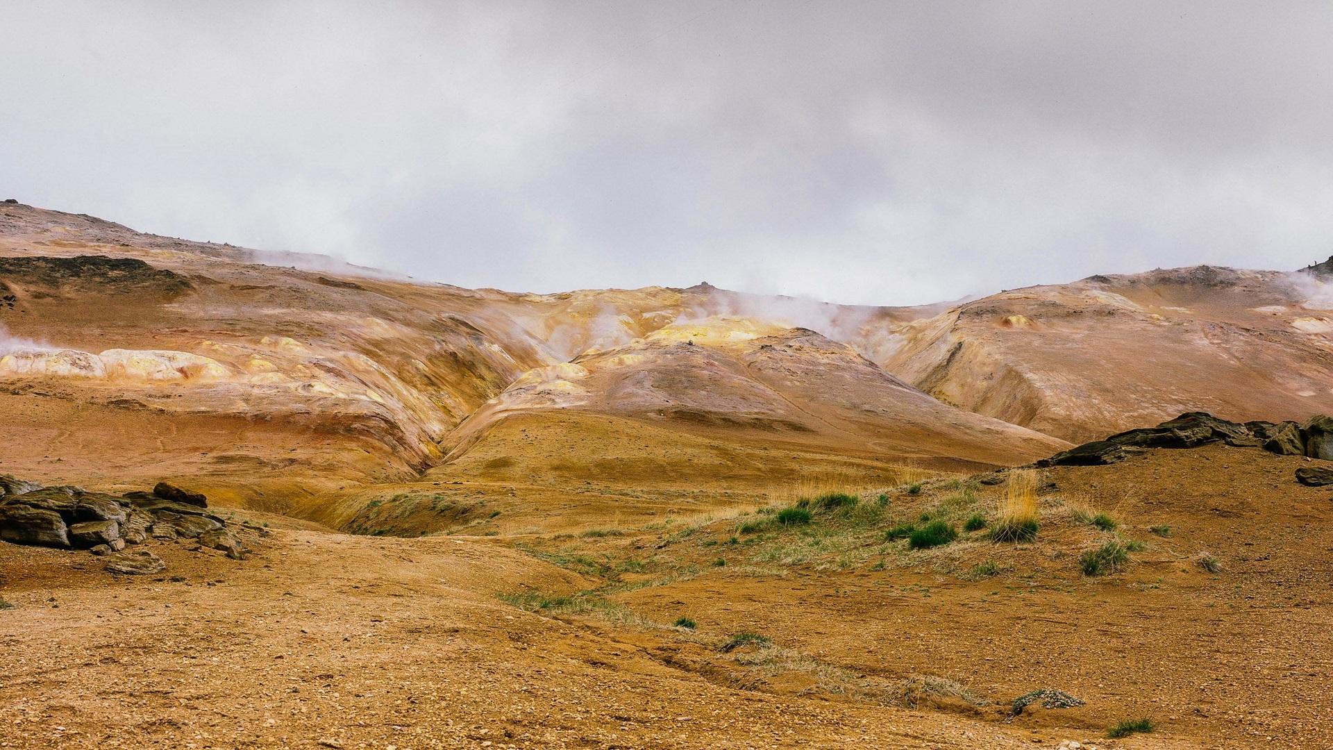 mountains geyser stones grass steam wallpaper