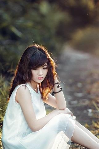 iPhone Обои Белое платье Азиатская девушка сидит на земле, траве, солнце