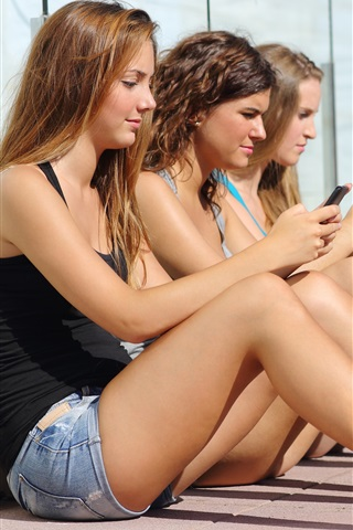 iPhone Wallpaper Three girls sit to use phones