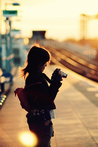 iPhone Wallpaper Little girl use camera, rail station, sunset