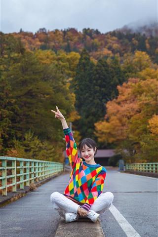 iPhone Fondos de pantalla Chica suéter colorido, pose, sentarse en el suelo, puente, árboles, otoño