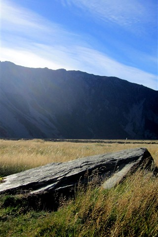 iPhone Wallpaper New Zealand, grass, rock, mountains, sun rays, blue sky