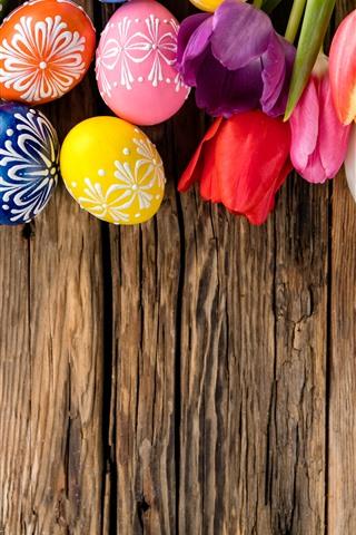 iPhone Fond d'écran Oeufs de Pâques colorés, tulipes, planche de bois